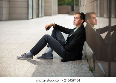 Young man with a mobile phone sitting at the wall