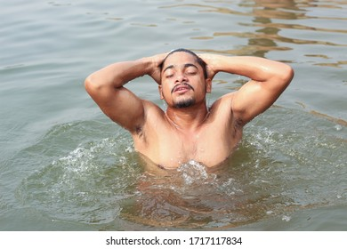 Young man model bathing in a river with a pose