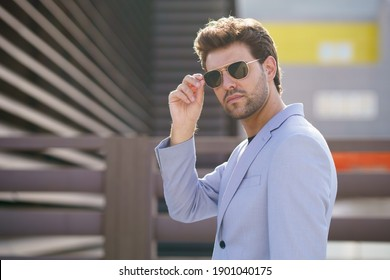Young man, model of fashion, wearing sunglasses in urban background