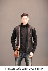 the young man model poses at a wall with the vintage camera on a shoulder