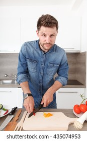 Young man in a modern kitchen preparing a vegetable salad. Nice man shows off his cooking skills.