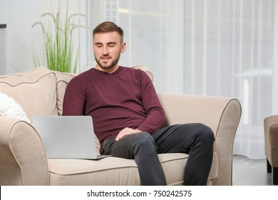 Young man with modern laptop on sofa at home