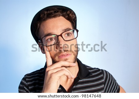 d9de4824068 Young man modern nerd thinking with hat and glasses wide angle close up  portrait on blue