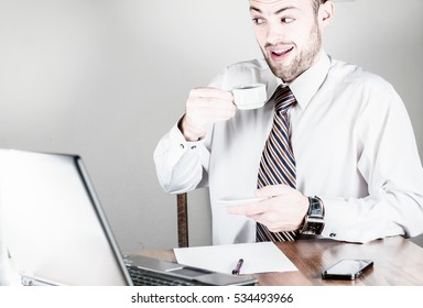 Young man in a modern office and drinks coffee