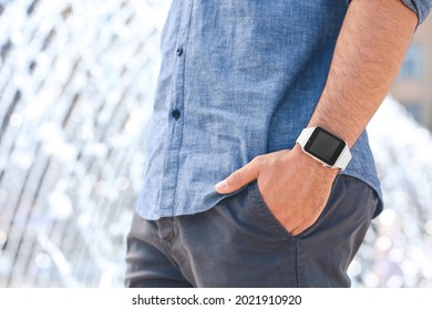 Young man with modern wristwatch outdoors