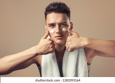 Young man with moisturizer on the face. Photo of smiling man on beige background. Grooming himself - Bilder