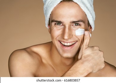 Young man with moisturizer on the face. Photo of smiling man on beige background. Grooming himself