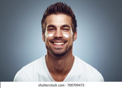Young man with moisturizer on the face