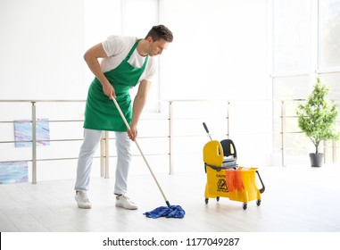 Young man with mop cleaning floor, indoors
