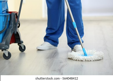 Young man with mop cleaning floor in the room, closeup