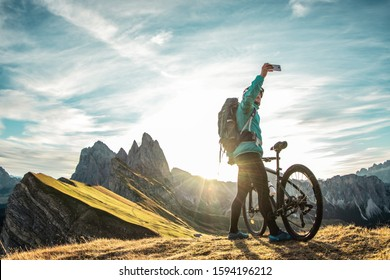 Young man with mountain bike taking selfies on Seceda mountain peak at sunrise. Puez Odle, Trentino, Dolomites, Italy.