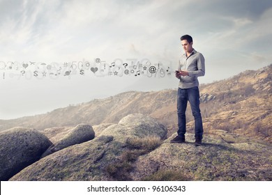 Young man in the mountains using a mobile phone and symbols coming out from it