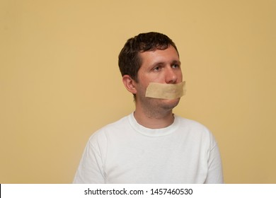 A young man with mouth bandage. Concept of freedom of speech, don't say.
