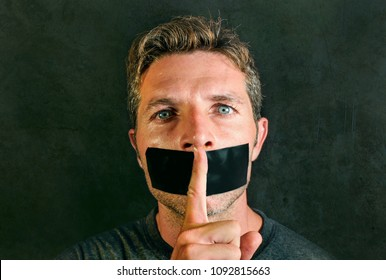 young man with mouth and lips sealed covered with adhesive tape in censorship coerced freedom of speech and forced silence and secrecy concept isolated on dark grunge background