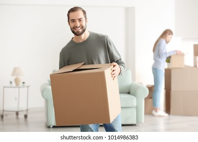 Young man with moving box in room at new home