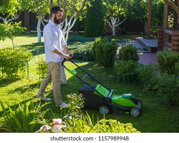 Young man mowing the lawn in the garden. Mowing the lawn on country house