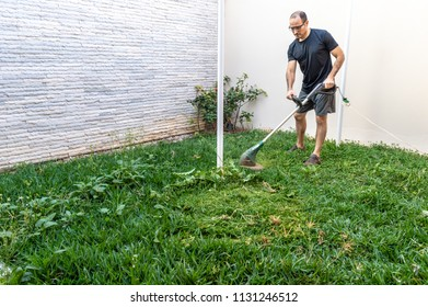 Young man mowing the lawn in his house