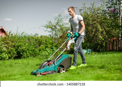 Young man mowing the lawn. Worker doing his job in backyard. Spending summer day in garden. Lawnmower standing on the background of private garden.