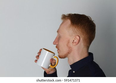 A young man with a mug of tea or coffee. He pleased. White background. Redhead male with white mug.