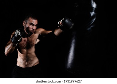 Young man with muscles training and hitting