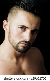 young man, muscular athlete with stylish hair and bearded face showing fit chest on black background. Training and healthy dieting