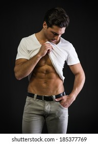 Young man with muscular body pulling up t-shirt on ripped abs