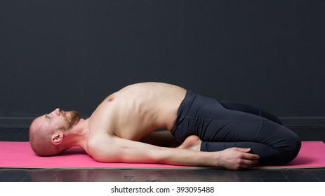 Young man with naked torso is  laying on the mat, bending the back, gray background