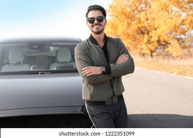 Young man near modern car on sunny day, outdoors