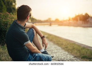 Young man near the river enjoying in sunny day.