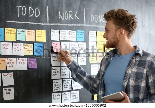 Young man near scrum task board in office