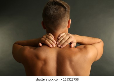Young man with neck pain on grey background