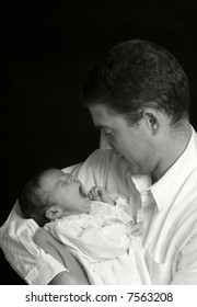 A young man with a newborn girl. Family, love, caring.