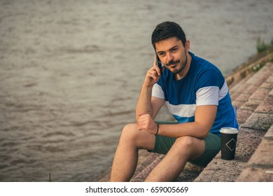 Young man next to river with coffee and mobile phone.