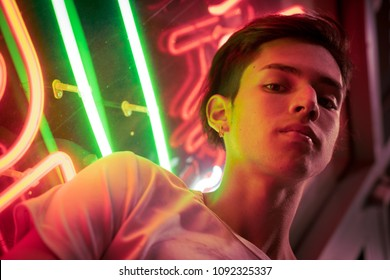 Young man night portrait, lit by neon.