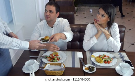 Young man not happy about his food and asking waiter to take it away