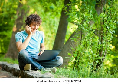 Young man with notebook sitting in the park