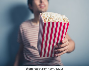 A young man is offering popcorn