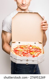 Young man offers opened box with tasty pizza holding in his hands