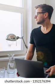 Young man in office with laptop looking out of the window on a sunny day