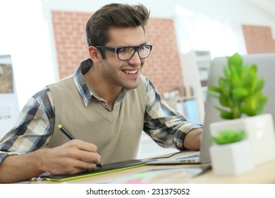 Young man in office using graphic tablet
