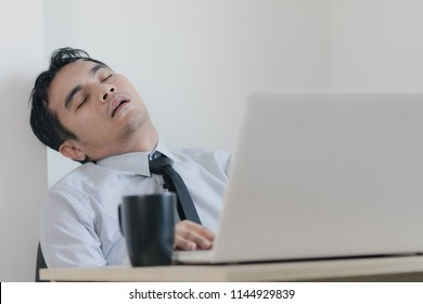 Young man officer sleeping and snoring on a chair his desk on working day