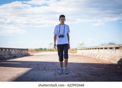 Young man with old camera walking on bridge.