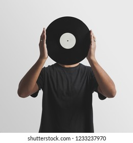 Young man olding a record in front of his face