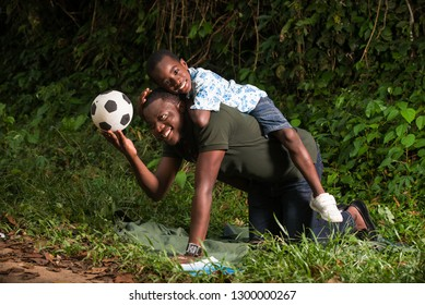 a young man on all fours in a park with his son on his back smiling at the camera.