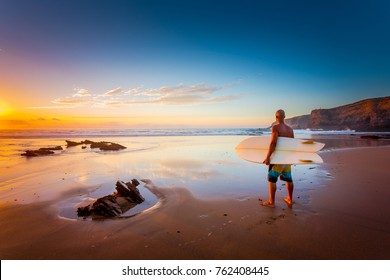 Young man on the beach with his surfboard looking at waves