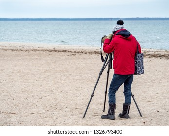 Young man on the beach wachting birds life using telescope