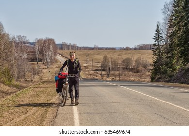 A young man on a bicycle, an athlete on an asphalt road. Around nature, forest. A man goes uphill with a bicycle. Spring day.