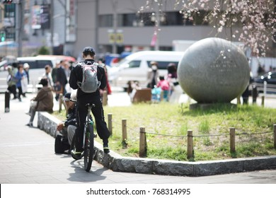 Young man on a bicycle on a street in a Japanese city