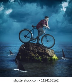 Young man on a bike standing on a rock in the middle of ocean surrounded by sharks.