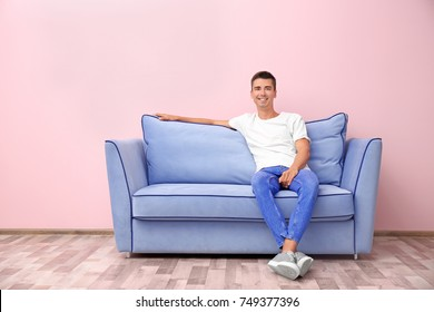 Young man on blue sofa near color wall